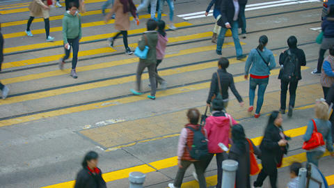 Pedestrians crossing a busy city street at a safety crosswalk in downtown Hong K Footage