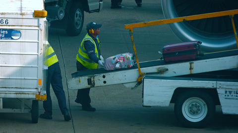 Ground crew unloading luggage from a commercial passenger plane at Macau Interna Footage