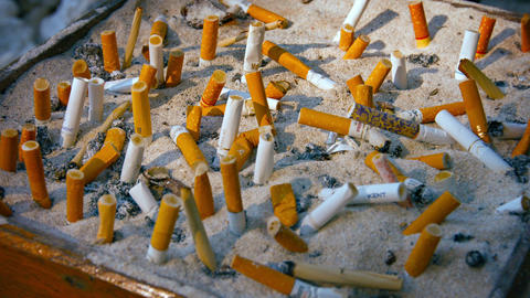 Cigarette butts in a designated smoking area Footage