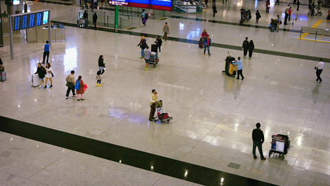 Passengers milling about with carts and luggage at the departures terminal Footage
