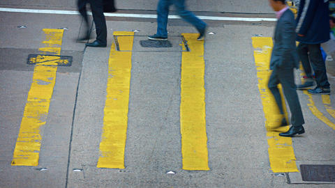 Pedestrians crossing urban street at a safety crosswalk in downtown Hong Kong Footage