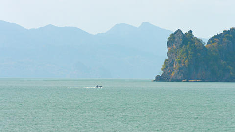 Small Motorboat Cruising past Rock Formations into Tropical Bay Footage
