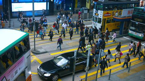 Crowd of pedestrians crossing a busy urban street in Hong Kong Footage