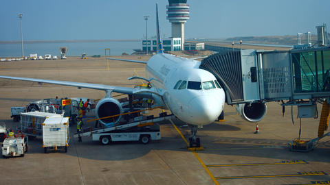 Ground crew unloading luggage from plane at Macau International Airport Footage