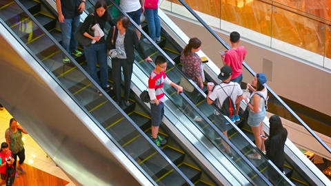 Shoppers riding alternately up and down parallel escalators Footage