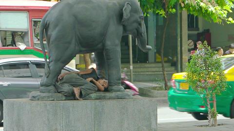 Homeless person sleeping beneath an elephant statue. Bangkok. Thailand Footage