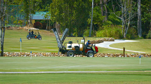 Maintenance utility vehicle drives past a putting green at golf course Live Action