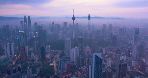 Night to day Aerial hyper lapse of Kuala Lumpur skyline covered with mist, Malaysia Live Action