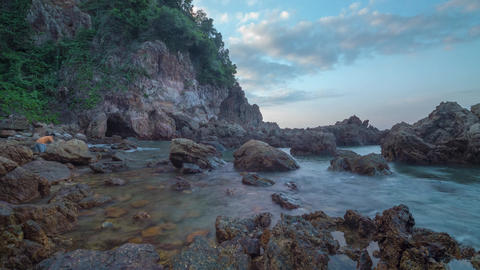 Motion time-lapse of sea waves hitting rocks as the sun goes down, Malaysia Live Action