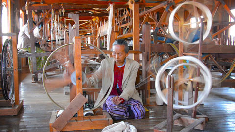 Old woman spinning thread on a manual device at Inle Lake. Myanmar Footage