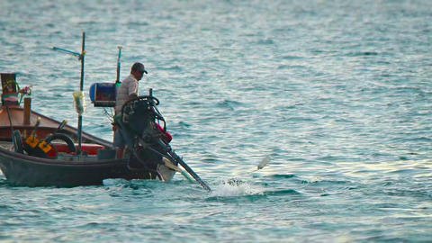 Fishermen in a traditional longtail boat. setting their nets Footage