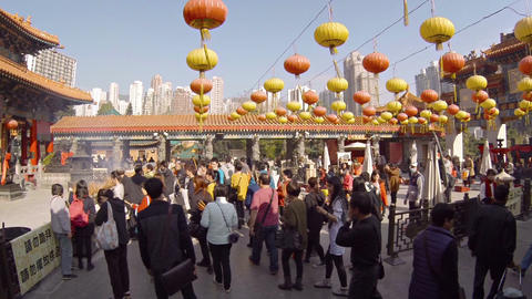 Worshippers praying and offering incense at Wong Tai Sin Buddhist temple Footage