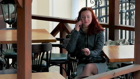 4K Girl Speaks on Cell Phone at Table in Empty Outdoor Cafe Footage