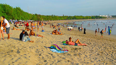People relax and take sun bath on sand of popular tourist attraction Kuta beach Live Action