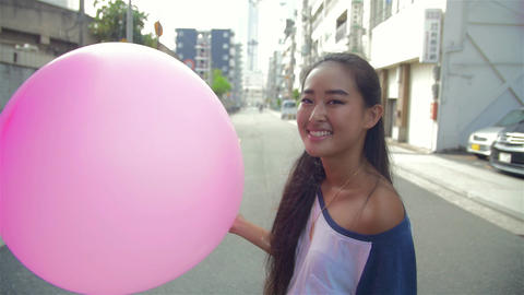 Fun attractive young Japanese women holding pink ballon Footage