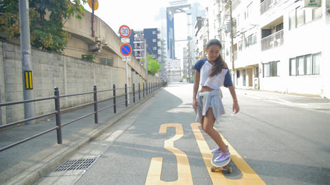 Young Carefree Japanese women riding Skateboard on the street slowmotion Footage