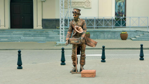 Living Statue With Hurdy-Gurdy in Steampunk Style Poses on Street Footage