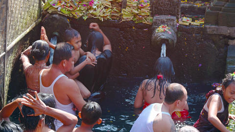 Families lined up to bathe in sacred springs of Tirta Empul temple in Bali Footage
