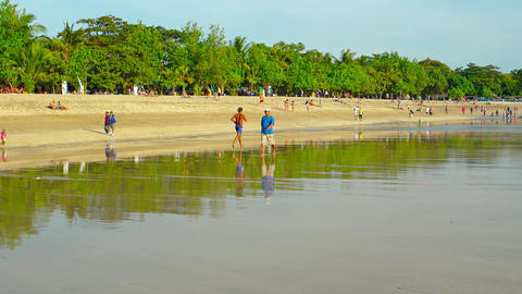 Running man. serfers and rested people on wide Kuta beach Footage