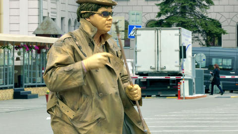 Living Statue Man Dressed in Sunglasses and Golden Suit Shows Floating Footage
