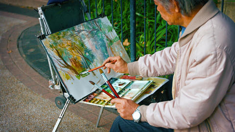 Talented street artist paints with watercolor on his easel in Hong Kong. China Footage