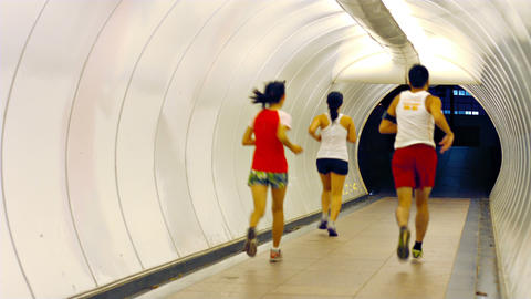 Joggers Running through a Brightly Lit Pedestrian Tunnel Footage