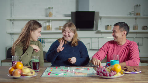 Diverse deaf friends playing board game in kitchen Live Action
