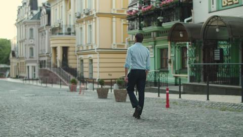 Back view businessman enjoying downtown. Businessman walking at empty street Live Action