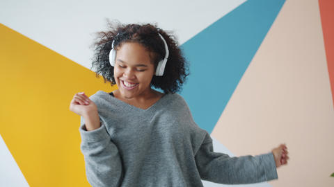 Slow motion of carefree African American lady dancing indoors wearing headphones Live Action