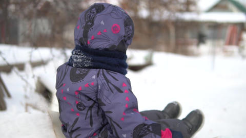A child rolls on a snow slide. Winter fun on the street. In the cold winter, the Live Action