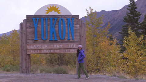 Yukon territory welcome sign - happy tourist woman in canadian territories Live Action