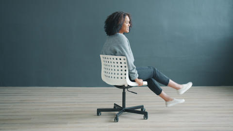 Portrait of playful African American girl spinning on office chair on gray Live Action