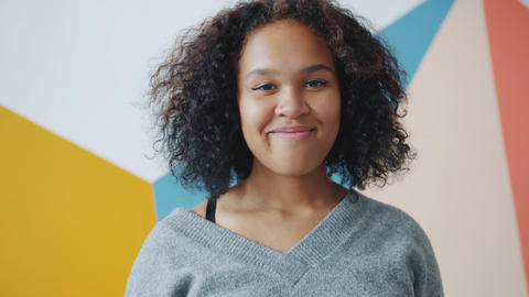 Portrait of attractive young Afro-American woman smiling on colorful background Live Action