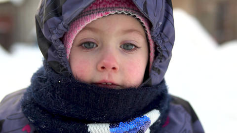 Faces of a child close-up outdoors in winter. In the cold winter, the child is Live Action