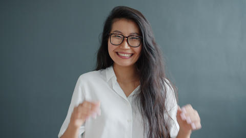 Slow motion of playful girl making funny faces having fun on gray background Live Action