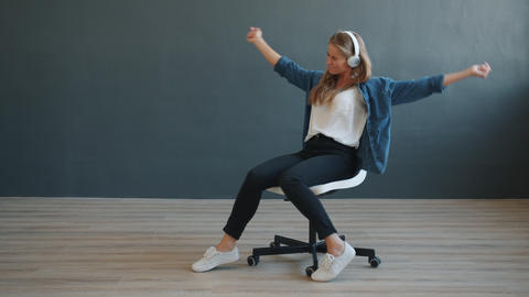 Carefree girl in headphones spinning on office chair wearing headphones dancing Live Action