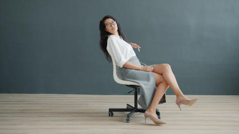 Pretty Asian businesswoman spinning on chair indoors on dark gray background Live Action