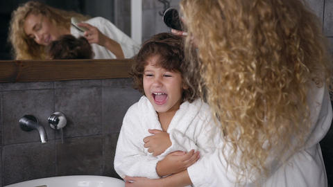 Caring and attractive young mum in white coat combing her curly hair her Live Action