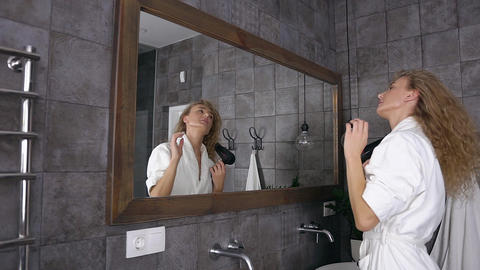 Attractive blonde woman in white bathrobe with long curly hair drying hair in Live Action