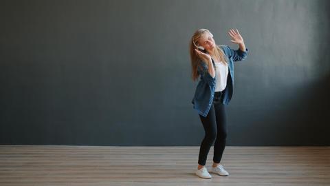 Happy young lady wearing wireless headphones dancing in studio having fun Live Action