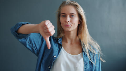 Portrait of good-looking woman showing dislike gesture raising arm with thumbs Live Action