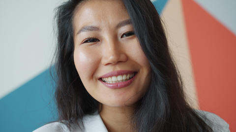 Close-up portrait of pretty Asian girl with long black hair smiling looking at Live Action