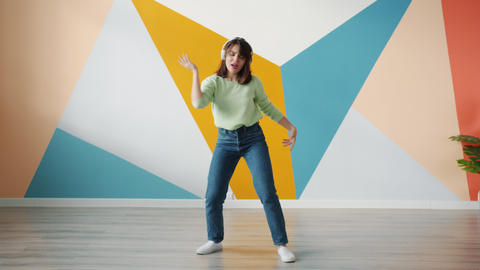 Cute young woman dancing indoors on colorful background wearing headphones Live Action