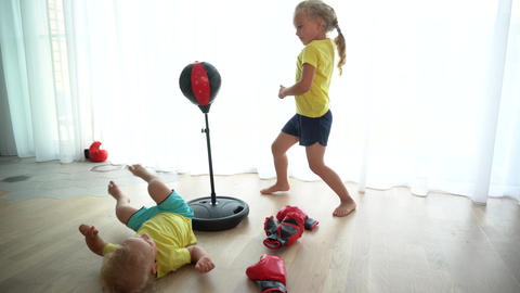 Big sister punching bag and fighting her little brother. Gimbal motion Live Action