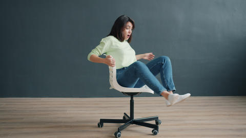 Portrait of carefree lady spinning on chair in studio enjoying funny activity Live Action