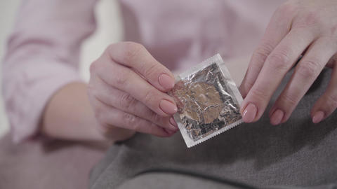 Close-up of female Caucasian hands holding condom. Adult woman holding Live Action