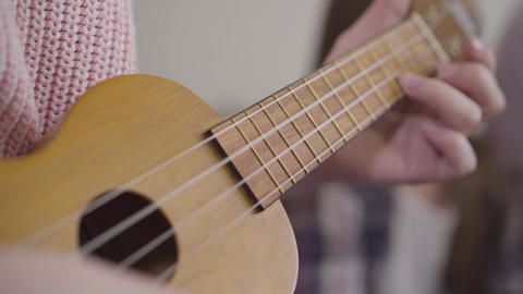 Extreme close-up of female Caucasian hands playing ukulele. Young talented girl Live Action