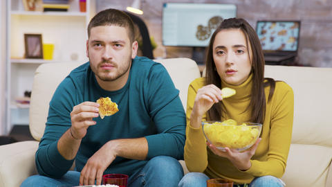 Scared couple while watching tv and eating junk food Live Action