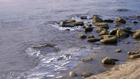 Water moving around stones at partly frozen lake shore Live Action