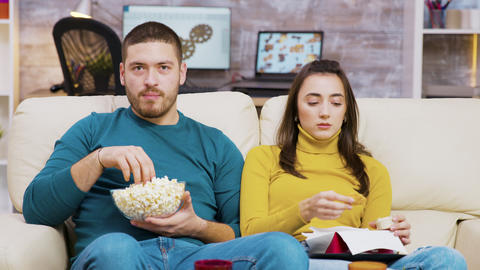 Scared couple watching tv eating pizza and popcorn sitting on couch Live Action
